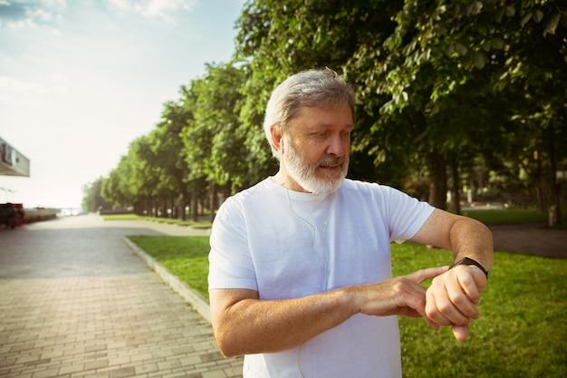 Starszy Mężczyzna Jako Biegacz Z Trackerem Fitness Na Ulicy Miasta. Kaukaski Model Mężczyzna Za Pomocą Gadżetów Podczas Joggingu I Treningu Cardio W Letni Poranek. Zdrowy Styl życia, Sport, Koncepcja Aktywności. Darmowe Zdjęcia