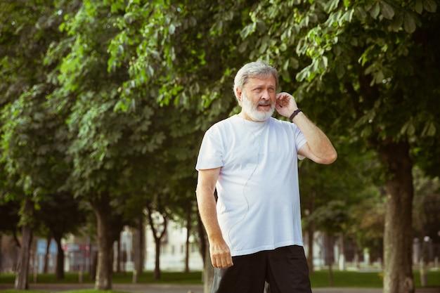 Starszy Mężczyzna Jako Biegacz Z Trackerem Fitness Na Ulicy Miasta. Darmowe Zdjęcia