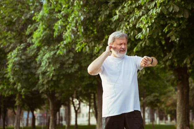 Starszy Mężczyzna Jako Biegacz Z Trackerem Fitness Na Ulicy Miasta Darmowe Zdjęcia