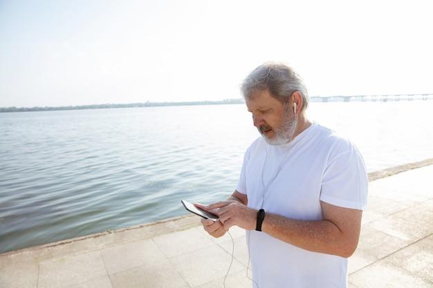Starszy Mężczyzna Jako Biegacz Z Trackerem Fitness Nad Rzeką. Kaukaski Model Mężczyzna Za Pomocą Gadżetów Podczas Joggingu I Treningu Cardio W Letni Poranek. Zdrowy Styl życia, Sport, Koncepcja Aktywności. Darmowe Zdjęcia