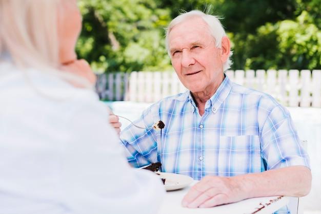 Starszy mężczyzna jedzenie ciasta na zewnętrznej werandzie Darmowe Zdjęcia