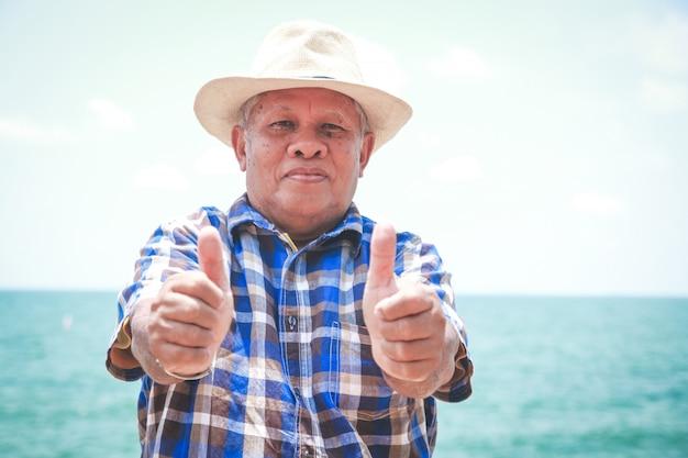 Starszy mężczyzna, kciuki do góry, dobre zdrowie, przyjdź na plażę, zrelaksuj się Premium Zdjęcia