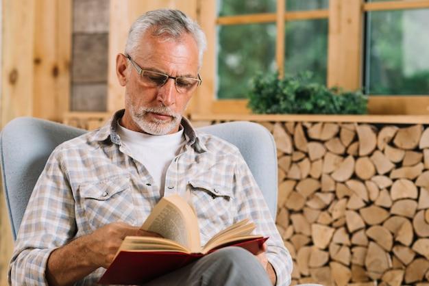 Starszy mężczyzna obsiadanie na ręki krzesła czytelniczej książce Darmowe Zdjęcia