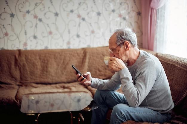 Starszy Mężczyzna Pije Poranną Herbatę I Sprawdza Pocztę Na Smartfonie Premium Zdjęcia