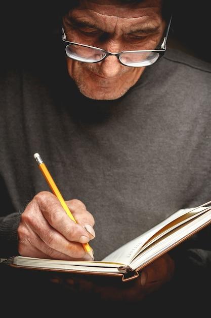 Starszy Mężczyzna Pisał Ołówkiem W Zeszycie Premium Zdjęcia