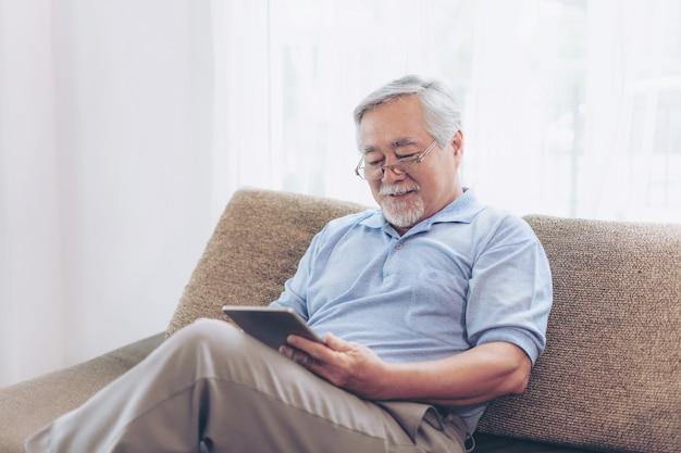 Starszy mężczyzna przy użyciu smartfona, uśmiechając się czuć się szczęśliwy na kanapie w domu - starszy starszych koncepcji Premium Zdjęcia