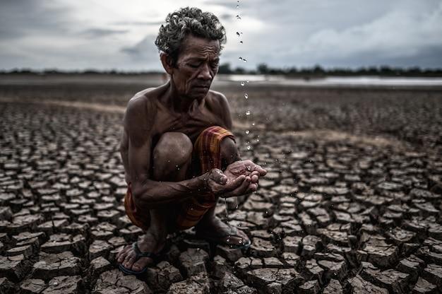 Starszy mężczyzna siedzący w deszczu w porze suchej, globalne ocieplenie, selekcja Darmowe Zdjęcia