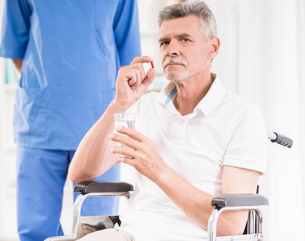 Starszy mężczyzna siedzi na wózku inwalidzkim i biorąc pigułki. Premium Zdjęcia
