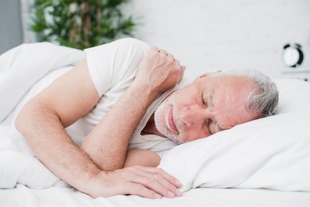 Starszy mężczyzna śpi w białym łóżku Darmowe Zdjęcia