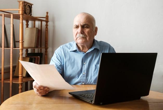 Starszy mężczyzna sprawdza handheld dokument Premium Zdjęcia