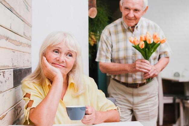 Starszy Mężczyzna Stojący Za Ukochaną Z Kwiatami Darmowe Zdjęcia