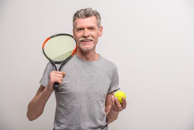 Starszy mężczyzna trener z rakietą tenisową i piłką tenisową. Premium Zdjęcia