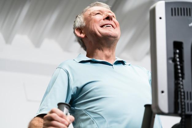 Starszy mężczyzna trenuje na przecinającym trenerze przy gym Premium Zdjęcia