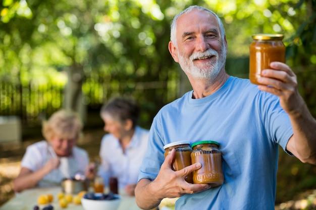 Starszy Mężczyzna Trzyma Puchar Morela W Kuchni Premium Zdjęcia