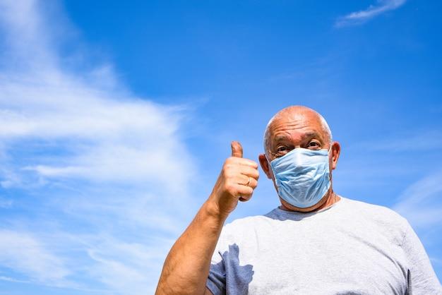 Starszy Mężczyzna Ubrany W Maskę Medyczną I Okulary Ochronne, Patrząc W Kamerę I Pokazuje Kciuk Do Góry. Premium Zdjęcia
