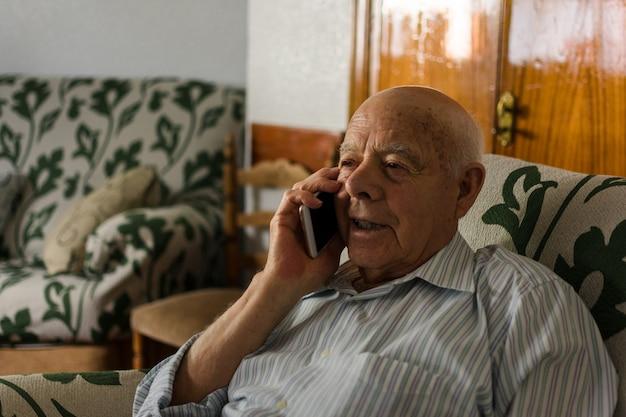 Starszy mężczyzna używa swojego smartfona w domu Premium Zdjęcia