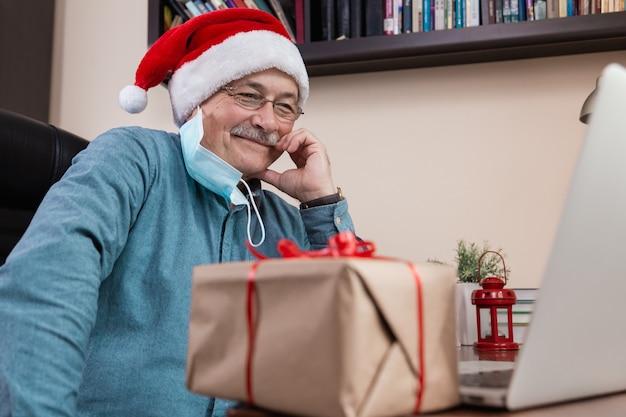 Starszy Mężczyzna W Czapce świętego Mikołaja Rozmawia Za Pomocą Laptopa Dla Przyjaciół I Dzieci Połączeń Wideo. Pokój Jest Odświętnie Urządzony. Boże Narodzenie W Okresie Koronawirusa. Premium Zdjęcia