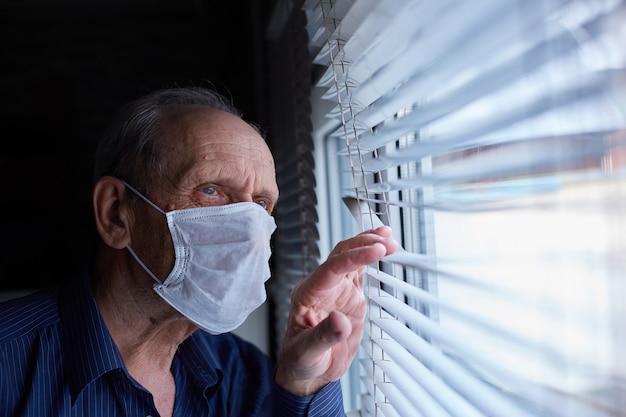 Starszy Mężczyzna W Masce Medycznej Znajduje Się W Kwarantannie I Samoizolacji Premium Zdjęcia