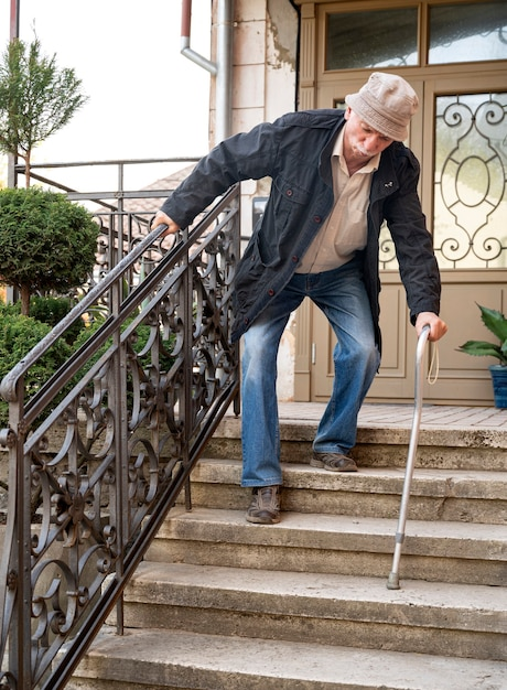 Starszy Mężczyzna W Masce Ochronnej Z Laską Schodzi Po Schodach Na Zewnątrz Premium Zdjęcia