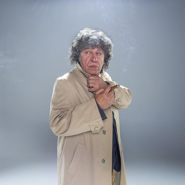 Starszy Mężczyzna Z Cygarem Jako Detektyw Lub Szef Mafii Na Szarym Studio Darmowe Zdjęcia