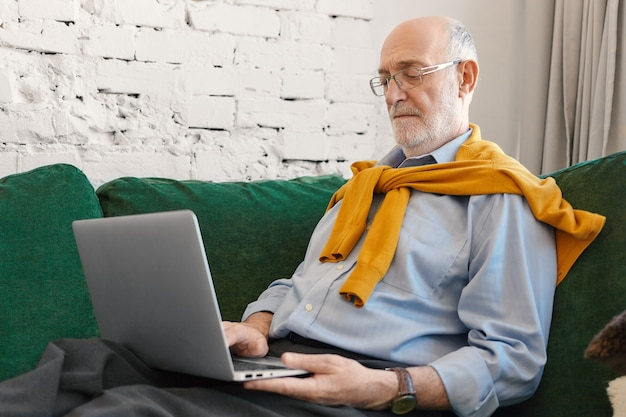 Starszy Mężczyzna Z łysą Głową I Brodą Za Pomocą Bezprzewodowego Szybkiego łącza Internetowego W Domu Na Laptopie. Poważny Skoncentrowany Dojrzały Biznesmen Czytanie Wiadomości Biznesowych Na Komputerze Przenośnym Na Kanapie Darmowe Zdjęcia