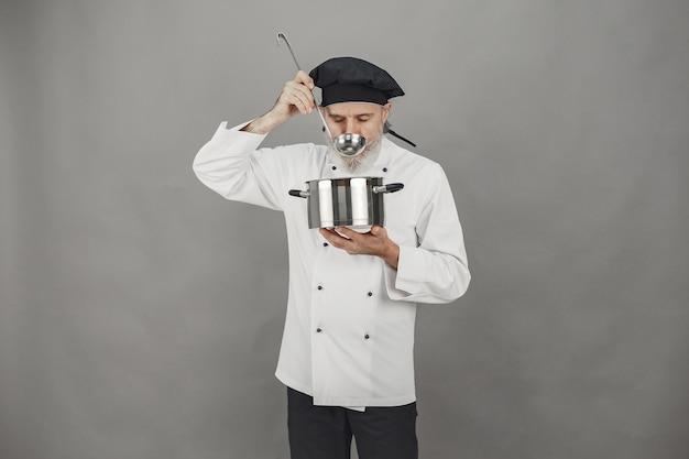 Starszy Mężczyzna Z Metalową Patelnią. Szef Kuchni W Czarnym Kapeluszu. Profesjonalne Podejście Do Biznesu. Darmowe Zdjęcia