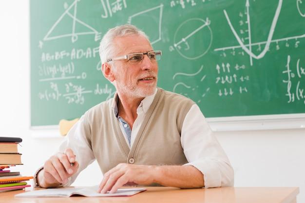 Starszy nauczyciel siedzi przy biurku w klasie Darmowe Zdjęcia