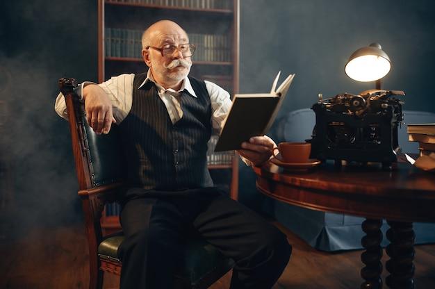 Starszy Pisarz Czyta Swoją Pracę Na Starej Maszynie Do Pisania W Domowym Biurze. Stary Człowiek W Okularach Pisze Powieść Literacką W Pokoju Z Dymem Premium Zdjęcia