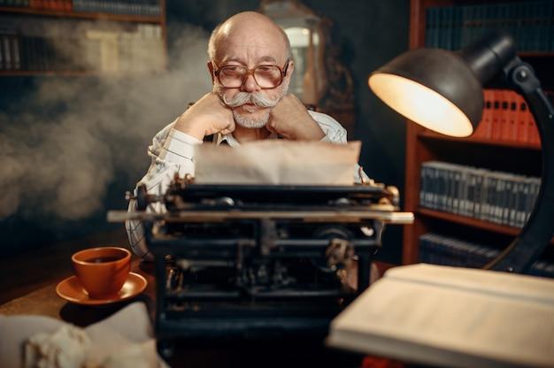 Starszy Pisarz Myśli O Starej Maszynie Do Pisania Premium Zdjęcia