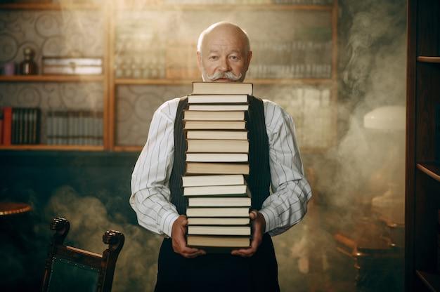 Starszy Pisarz Posiada Stos Książek W Biurze Domowym Premium Zdjęcia