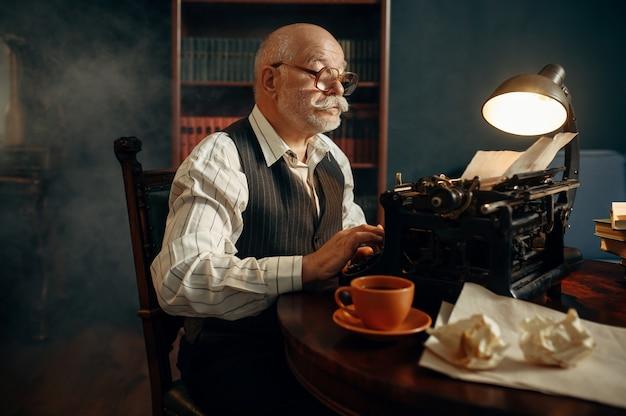 Starszy Pisarz Pracuje Na Starej Maszynie Do Pisania W Swoim Domowym Biurze. Stary Człowiek W Okularach Pisze Powieść Literacką W Pokoju Z Dymem Premium Zdjęcia