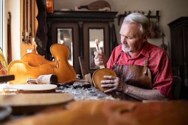 Starszy Stolarz Montujący Elementy Instrumentu Skrzypcowego W Swoim Warsztacie Stolarskim Darmowe Zdjęcia