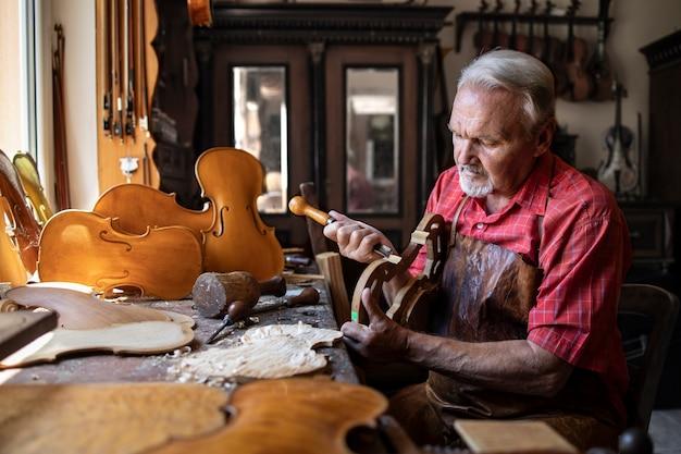 Starszy Stolarz, Rzemieślnik Rzeźbiony W Drewnie W Swoim Staromodnym Warsztacie Darmowe Zdjęcia