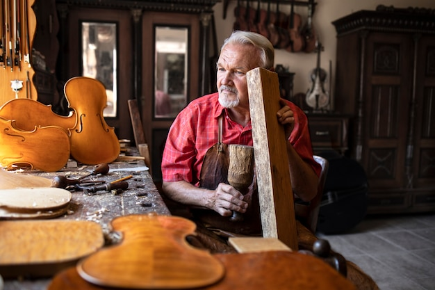 Starszy Stolarz Sprawdzający Jakość Dźwięku Materiału Drzewnego W Swoim Staromodnym Warsztacie Stolarskim Darmowe Zdjęcia