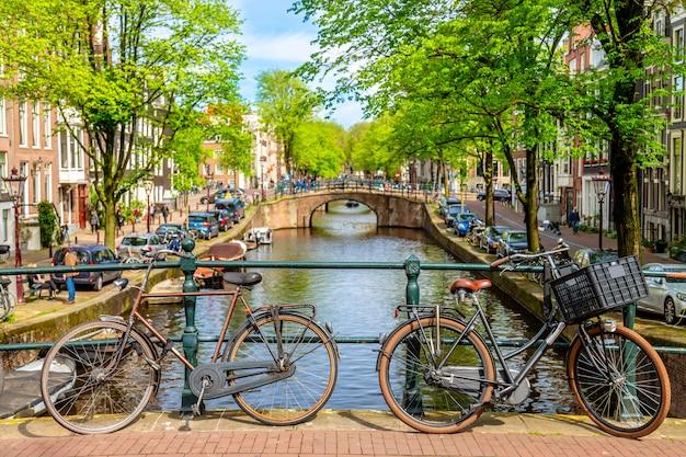 Stary Bicykl Na Moscie W Amsterdam, Holandie Przeciw Kanałowi Podczas Lato Słonecznego Dnia. Premium Zdjęcia