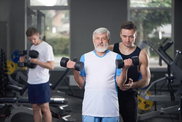 Stary człowiek pozuje z dumbbells, trenera szkolenie. Premium Zdjęcia
