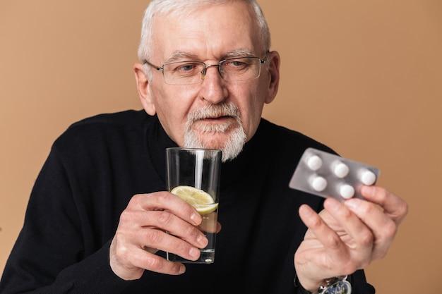 Stary Człowiek Trzyma Tabletkę Z Portretem Tabletki Premium Zdjęcia