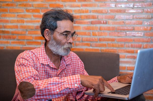 Stary Człowiek Uczy Się Korzystać Z Laptopa W Domu, Starszy Mężczyzna Korzysta Z Komputera W Domu Premium Zdjęcia
