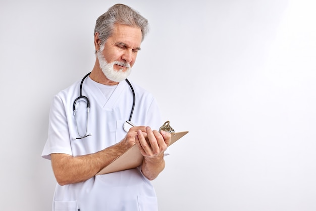 Stary, Doświadczony Kaukaski Lekarz Pisze Objawy I Diagnozuje Premium Zdjęcia
