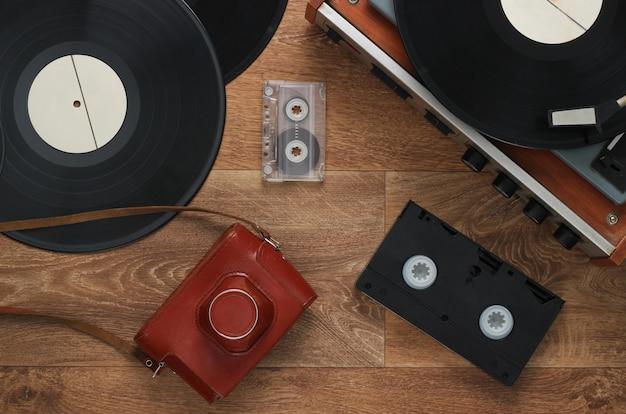 Stary Gramofon, Kasety Wideo, Kaseta Magnetofonowa, Staromodna Kamera Filmowa Na Podłodze. Retro Media Lata 80. Widok Z Góry Premium Zdjęcia