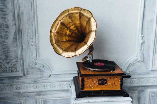 Stary gramofon z głośnikiem tubowym stoi przeciwko starożytnemu Premium Zdjęcia