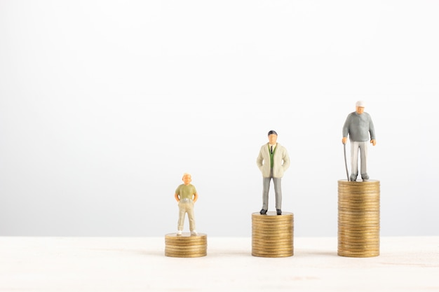 Stary i młody człowiek stoją na stosach złotych monet na białym tle Premium Zdjęcia