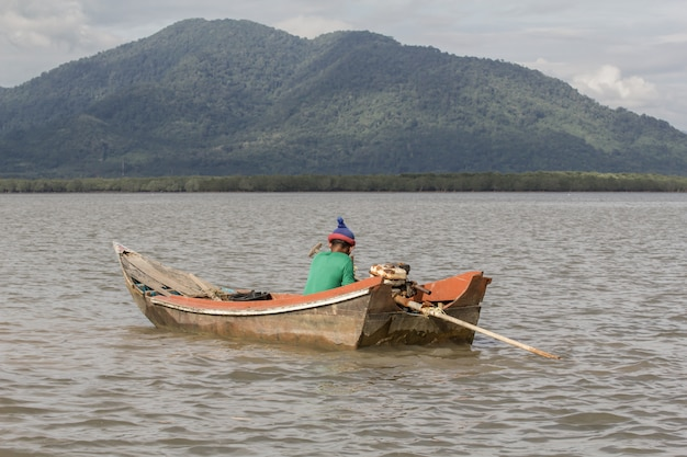 Stary rybak na starej drewnianej łodzi. Premium Zdjęcia