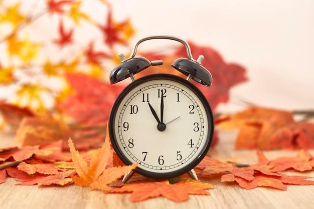 Stary Zegar Na Jesień Liściach Na Drewnianym Stole Premium Zdjęcia