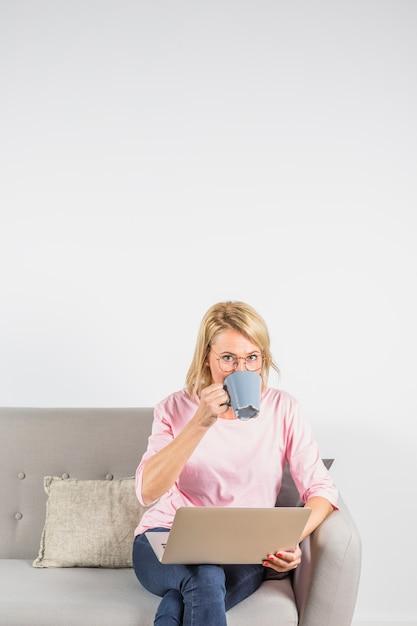 Starzejąca się kobieta pije od filiżanki na kanapie w różanej bluzce z laptopem Darmowe Zdjęcia