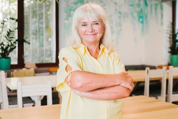 Starzejąca się szczęśliwa kobieta stoi w domu ono uśmiecha się Darmowe Zdjęcia