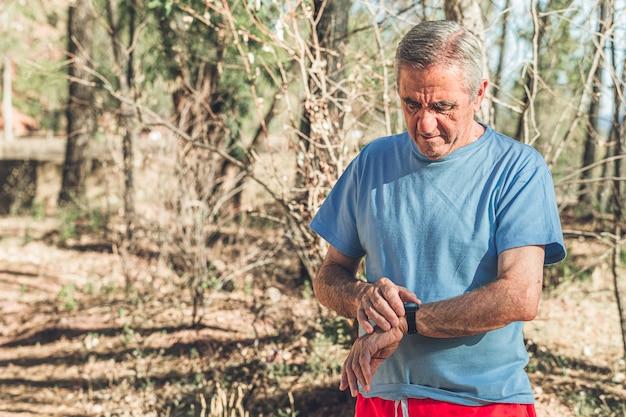Starzejący się jogger sprawdza zegarek po uruchomieniu Premium Zdjęcia