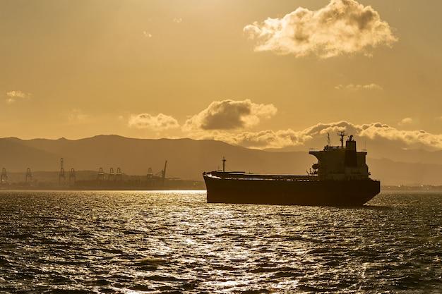 Statek Towarowy Na Drodze O Zachodzie Słońca. Import I Eksport Logistyki. Premium Zdjęcia
