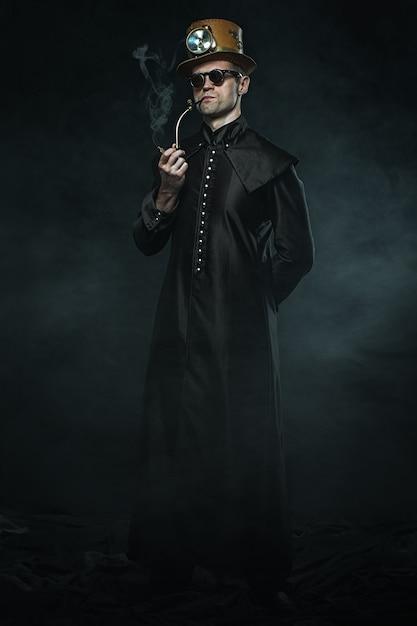 Steampunk Mężczyzna W Długim Płaszczu Pali Fajkę. Premium Zdjęcia
