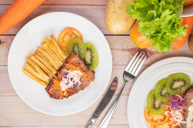 Stek Rybny Z Frytkami, Kiwi, Sałatą, Marchewką, Pomidorami I Kapustą W Białym Naczyniu. Darmowe Zdjęcia